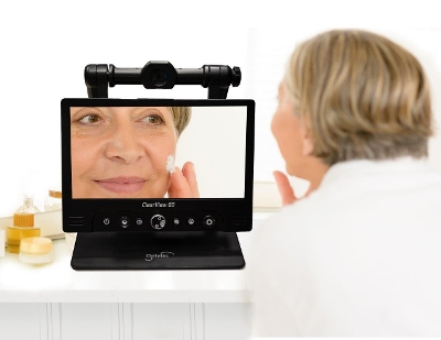 Image of Person using the ClearView GO to enlarge her face on a large monitor while putting on cream